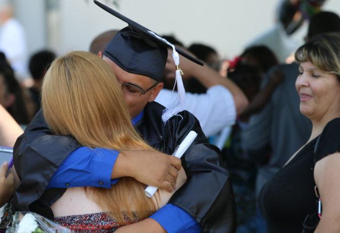 Graduate hugging loved one
