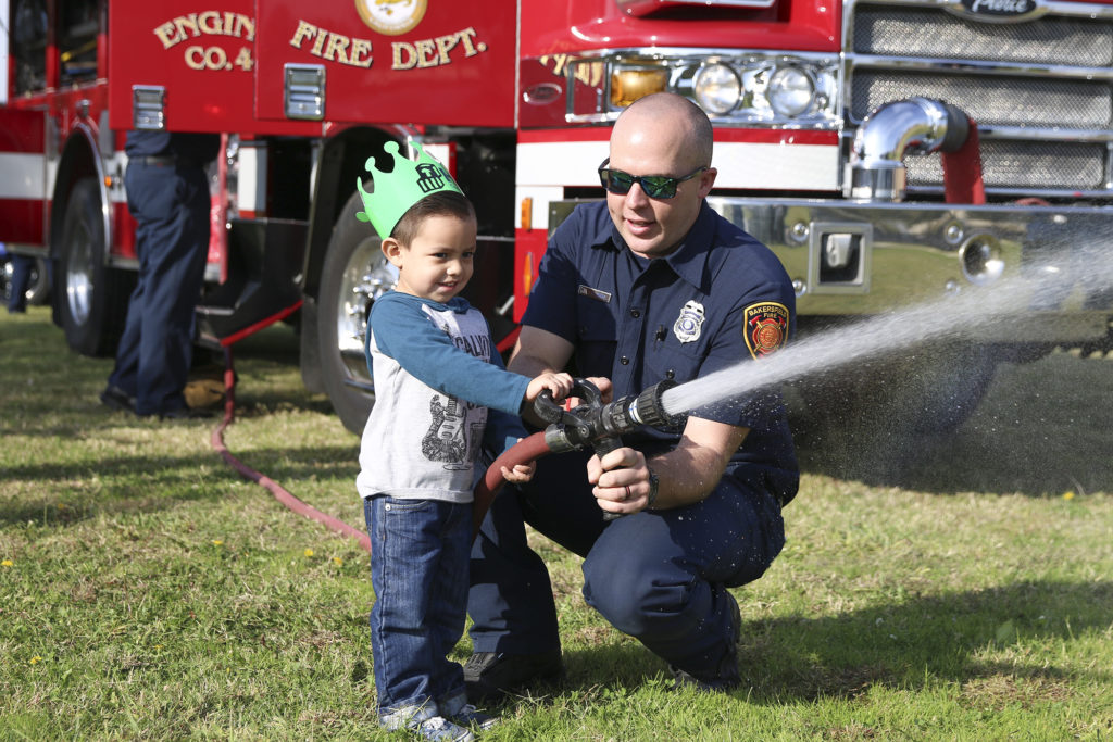 Fireman showing a kid how to hold a hose